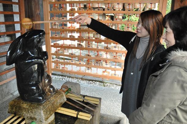神聖なる手水舎で無作法に顔を洗う海外観光客